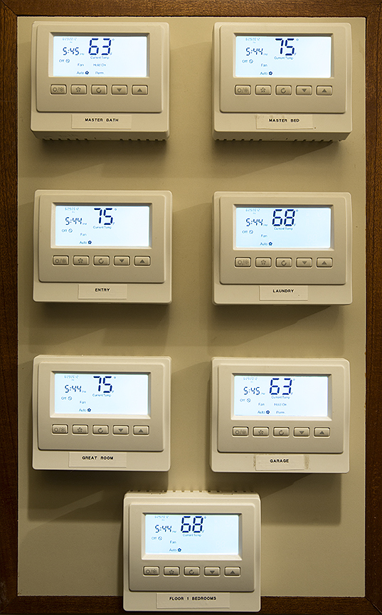 Control4 thermostats installed in utility closet to reduce wall clutter in rooms